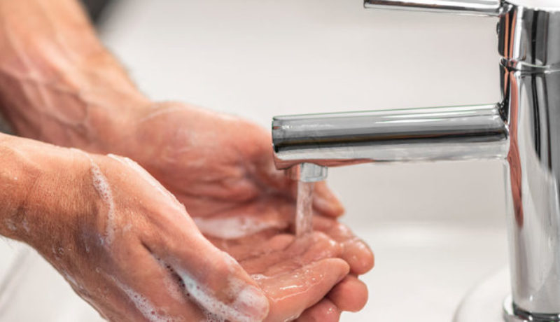 Washing hands man rinsing soap with running water at sink, Coronavirus prevention hand hygiene.