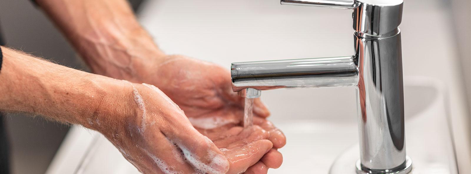 Washing hands man rinsing soap with running water at sink, Coronavirus prevention hand hygiene.