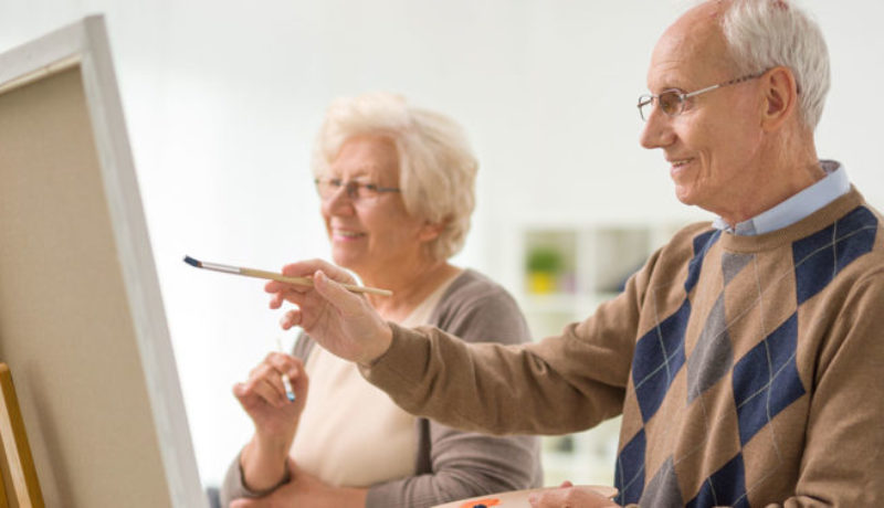 Older man and woman painting something on a canvas with paintbrushes at memory care facility